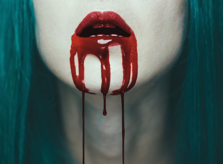 female face closeup: Blood is flowing from the mouth of a woman. Close-up image of red lips. Halloween or horror theme