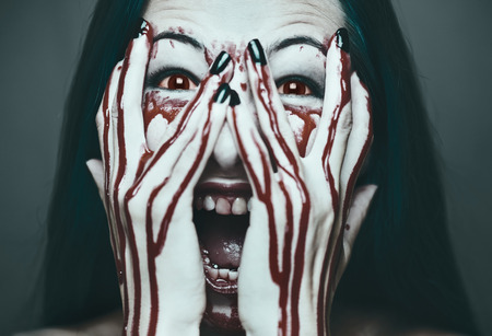 pretty face: Spooky young woman screaming, her face and hands in blood. Halloween and horror theme. Monochrome image