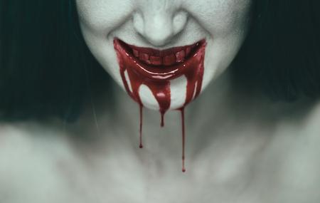 不気味な女は笑みを浮かべて、血液中女性の口の中。ハロウィーンやホラーのテーマ 写真素材