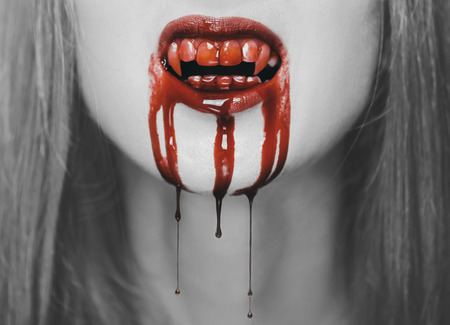 female face closeup: Spooky vampire woman, close-up of mouth with teeth in red blood. Halloween or horror theme. Black and white image with red elements