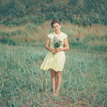 female beauty: Beautiful young woman standing with bouquet of yellow flowers in summer field
