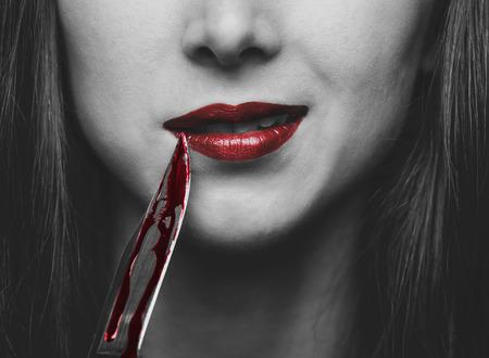 Glimlachend gevaarlijke jonge vrouw met een mes in het bloed. Halloween of horror thema. Zwart-wit beeld met rode elementen
