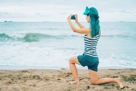 Beautiful young woman with blue hair taking photographs of sea in summer Stock Photo