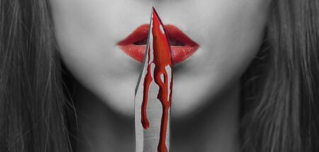 red lip: Dangerous young woman kissing a knife in blood. Halloween or horror theme. Black and white image with red elements