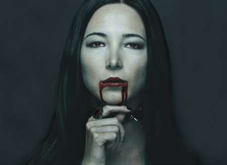 horror: Dark portrait of beautiful young woman with vampire halloween make-up. Halloween or horror theme Stock Photo