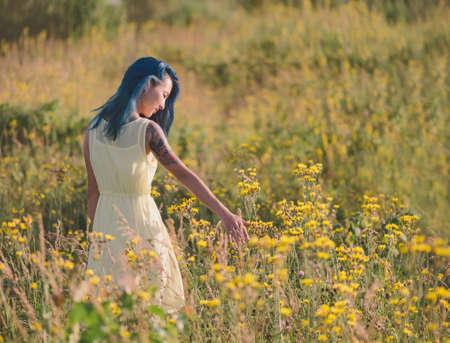 campo de flores: Joven y bella mujer con el pelo azul que recorre en campo de flores en verano