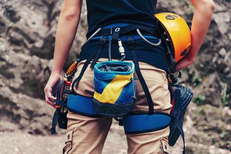 escalando: Mujer de pie con el equipo que sube y casco delante de la roca de piedra al aire libre, traseros. De cerca. La cara no es visible Foto de archivo