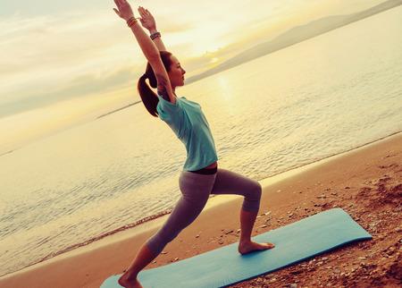beach mat: Beautiful young woman practicing yoga on mat on sand beach near the sea on sunset Stock Photo