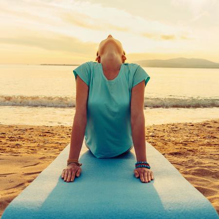 Jovem, mulher, praticar yoga em cima enfrentando o cão levanta na praia perto do mar no por do sol, vista de frente