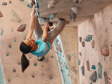Free climber young woman climbing on a rock wall indoor, bouldering Banque d'images