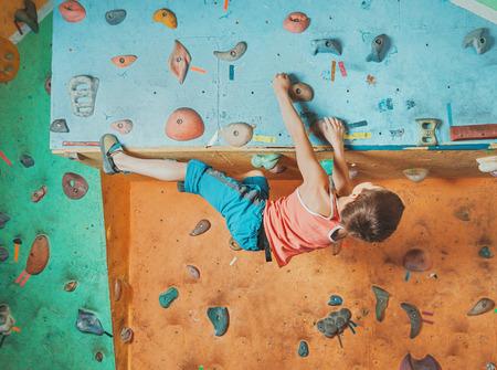 niño escalando: Escalador libre niño de practicar en los cantos rodados artificiales en el gimnasio, búlder