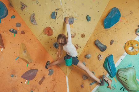 niño trepando: Escalador libre niña practicando en rocas artificiales en el gimnasio
