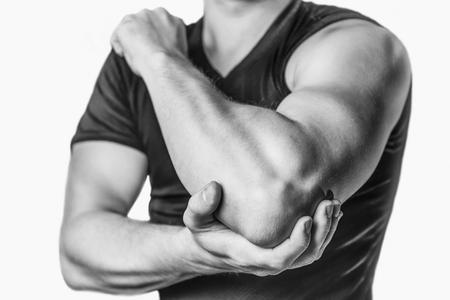 masaje deportivo: El hombre sostiene la articulación del codo, dolor agudo en el codo. Imagen monocromática, aislado en un fondo blanco Foto de archivo