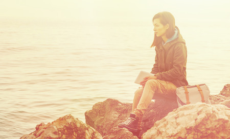 coastlines: Traveler young woman with digital tablet and backpack sitting on stone coast. Image with sunlight effect