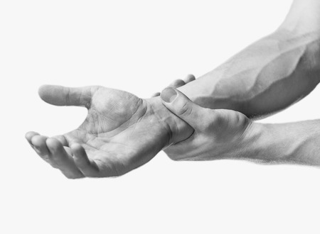 carpal: Pain in a male wrist. Man holds his hand, close-up image. Monochrome image, isolated on a white background Stock Photo