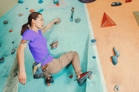 free climber: Free climber young woman training on artificial boulder wall indoors Stock Photo