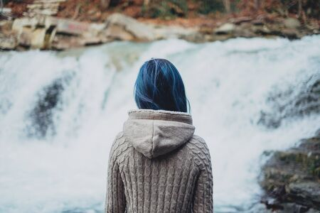 blue hair: Traveler woman with blue hair looking at beautiful waterfall, rear view