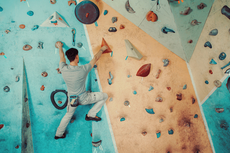 man climbing: Young man climbing on artificial boulders wall indoor, rear view Stock Photo