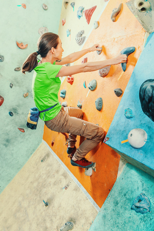 free climber: Free climber young woman training on artificial boulder wall in gym Stock Photo