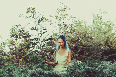 big flower: Beautiful girl with blue hair walking in fairy forest, girl standing near a big flower. Toning color Stock Photo