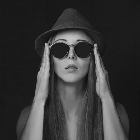 hair and beauty: Beautiful girl with long hair in round sunglasses and hat. Fashion and beauty. Black and white image