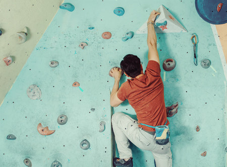 free climber: Free climber young man climbing artificial boulder in gym, rear view