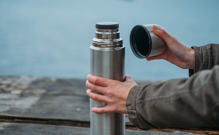 thermos: Unrecognizable woman opening a thermos on wooden table, view of hands Stock Photo