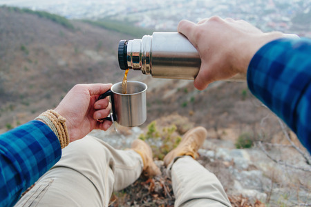 thermos: Hiker man sitting in mountains and pouring tea from thermos to cup. Point of view shot