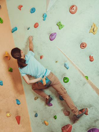 magnesia: Free climber young woman coating her hand in powder chalk magnesium and climbing artificial boulder indoors Stock Photo