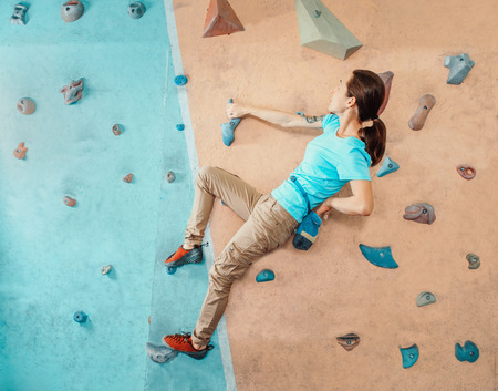 free climber: Free climber young woman coating her hand in powder magnesium and climbing artificial boulders indoors