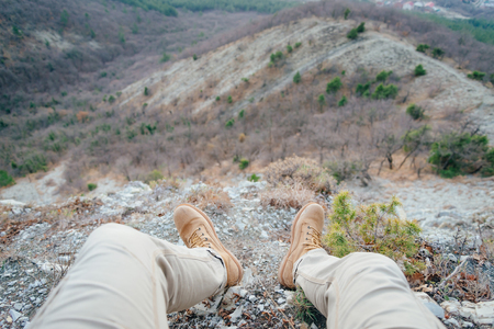 point of view: Man resting in the mountains, view of legs. Point of view shot