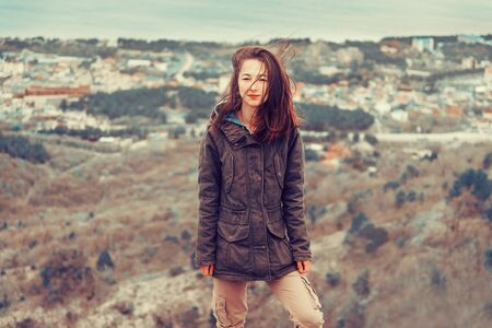 parka: Young woman dressed in parka jacket and cargo pants standing on hill on background of town
