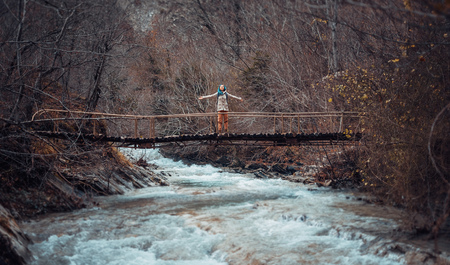 raised arms: Happy hiker young woman standing with raised arms on bridge Stock Photo