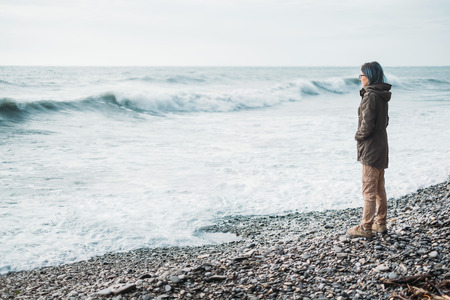 waves  pebble: Traveler young woman standing on pebble coast and looking at sea waves in windy weather Stock Photo
