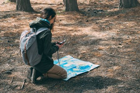orienteering: Hiker young woman with backpack searching direction with a compass and map in the forest