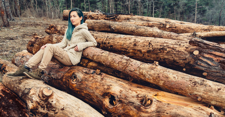 lumbering: Young woman with blue hair sitting on stack of tree trunk, girl resting outdoor Stock Photo