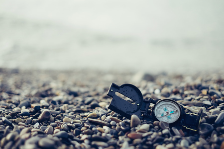 magnetic stones: Travel compass on pebble coast, free space