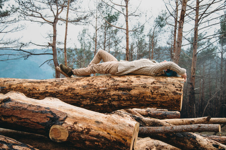 woman laying: Beautiful young woman with blue hair lying on fallen tree trunk. Girl resting outdoor