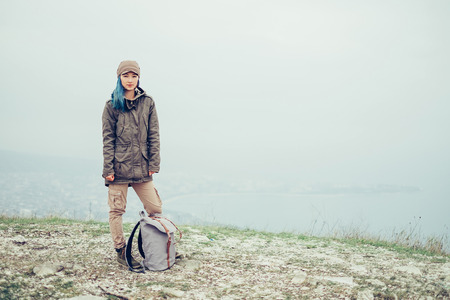 hair part: Beautiful traveler girl with blue hair standing with backpack outdoor and looking at camera. Free space in right part of the image