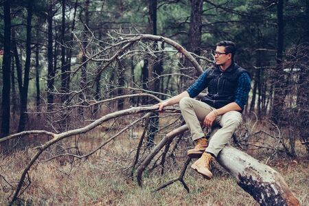 explorer man: Explorer young man sitting on fallen tree in the forest. Traveler man resting outdoor Stock Photo