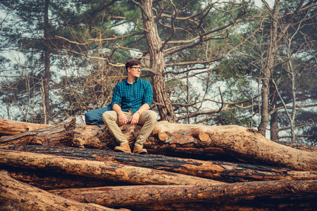 explorer man: Explorer traveler young man with backpack sitting on felled tree trunk in the pine forest outdoor in summer