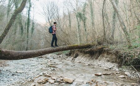 river trunk: Hiker young man with backpack crossing river on fallen tree trunk in the forest Stock Photo