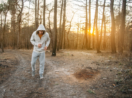 rugged man: Sporty young man in hoodie running on rugged terrain among pine trees in the forest at sunset Stock Photo