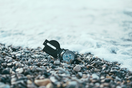 waves  pebble: Travel compass on pebble coast near the sea waves