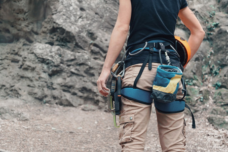 safety harness: Unrecognizable woman rock climber wearing in safety harness with climbing equipment and helmet outdoor