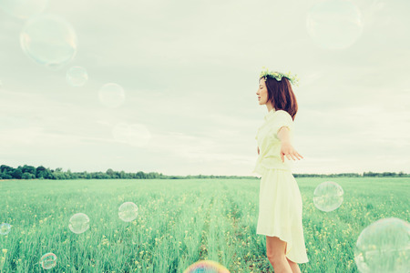 Happy beautiful girl in flower wreath walking on summer meadow among soap bubbles