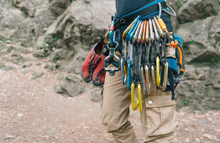 safety harness: Unrecognizable woman rock climber wearing in safety harness with quickdraws and climbing equipment outdoor