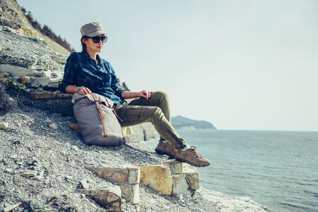 descansando: Traveler young woman sitting on stone coast with backpack and enjoying view of sea in summer
