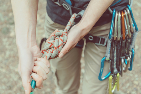 safety harness: Unrecognizable climber woman wearing in safety harness with quickdraws doing rope eight knot and preparing to climb
