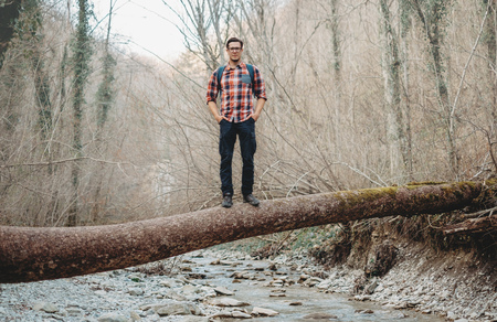river trunk: Hiker young man with backpack standing on fallen tree trunk over the mountain river in forest